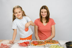 Six-year girl puts on pizza tomatoes under the supervision of mum Stock Photo