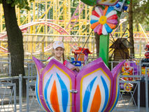 Six-year girl riding on a carousel, sitting in stylized floret Royalty Free Stock Photo