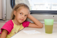 Six-year girl thoughtfully and tired sitting on train at the table in the second-class compartment Stock Images