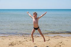 Six-year-old boy in black speedo jumping into the sea and shouts. Six-year-old boy in black speedo jumping into the sea and yells. Jump high off the ground Stock Image