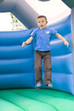 Six year old boy bouncing. A candid portrait of a cute six year old boy jumping on a bouncy castle moonwalk Royalty Free Stock Photo