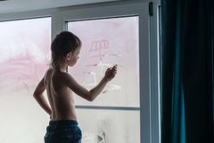 Six-year-old boy wearing jeans draws a boat on a misty window standing on the windowsill at home. Six-year-old boy draws a boat on a misty window standing on Stock Photo