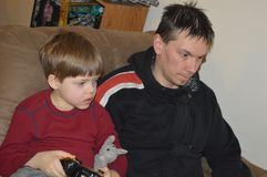 Single father and son play video game royalty free stock images
