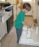 Boy taking silverware out of dishwasher royalty free stock photography