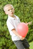 Six year old boy holding a balloon Royalty Free Stock Image