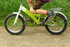 Six year old boy learning to ride a bicycle, feet close up Stock Photo