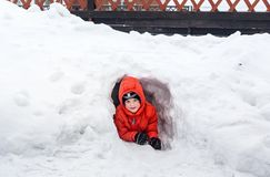 Six-year-old boy looking out from a snow. Cave Stock Photos