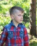 Six-year-old boy looks askance at the lens in the  garden Royalty Free Stock Photography