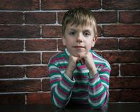 Six-year-old boy with a malicious expression. Looks at the camera Royalty Free Stock Photo