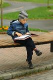 Six year old boy reading a book on the bench in the park Stock Photo