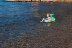 Six-year-old boy swims on an inflatable rubber mattress on the sea stock photos