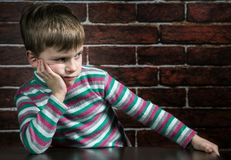 Six year old boy with a thoughtful expression. On the wall background Stock Photo