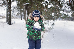 The six-year-old boy is in the wood. Around a pine. The kid holds snow in hand and blows on him Royalty Free Stock Photos
