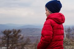 Six-year-old child in a red down jacket stands in the mountains with his back to the camera stock photo