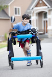Six year old disabled boy in walker on street Stock Photography