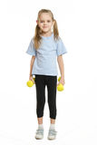 Six year old girl athlete standing with dumbbells Royalty Free Stock Photos