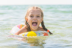 Six year old girl bathing in the sea with his mouth open in pleasure Stock Image