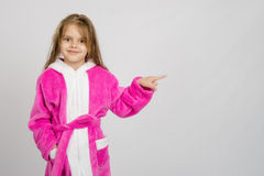 Six year old girl in bathrobe pointing at empty space Royalty Free Stock Photos