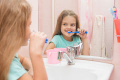 Six year old girl brushing the front teeth look in the mirror in the bathroom Stock Photos