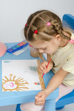 Six year old girl draws a paint something in the picture Royalty Free Stock Photo