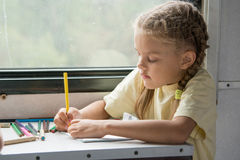 Six year old girl draws pencils in second-class train carriage Stock Photos