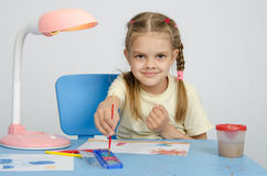 Six year old girl dunks brush in the paint Royalty Free Stock Images
