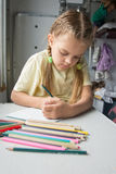 Six year old girl with enthusiasm draws pencils in second-class train carriage Royalty Free Stock Photo