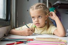 Six year old girl lost in thought looked out the window drawing pencils in second-class train carriage Stock Photo