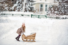 Six year old girl playing with vintage sleds in winter Royalty Free Stock Image