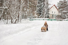 Six year old girl playing with vintage sleds in winter Stock Photography