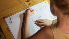 A six year old girl is practicing writing in a notebook. royalty free stock photo