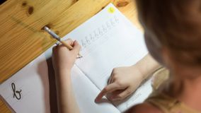 A six year old girl is practicing writing in a notebook. stock image