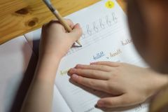 A six year old girl is practicing writing in a notebook. royalty free stock photos