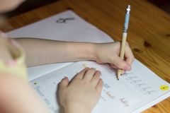 A six year old girl is practicing writing in a notebook. royalty free stock photography