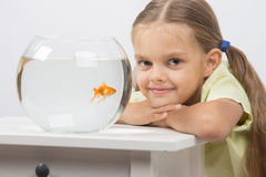 Six year old girl put her head on the handle sitting at the table with an aquarium with goldfish Stock Photo