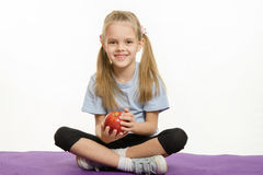 Six year old girl sitting on a rug with an apple hands Royalty Free Stock Photography