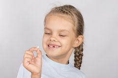 Six year old girl with a smile looking at the fallen baby tooth Stock Image