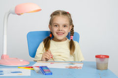 Six year old girl smiling happily, drawing the table Royalty Free Stock Images
