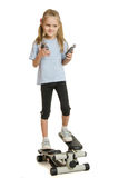 Six year old girl on a step simulator with expander in the hands of Stock Images
