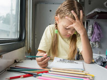 Six year old girl thoughtfully draws pencils in second-class train carriage Royalty Free Stock Image