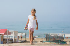 Six year old girl walking on wooden flooring from the sea home. Six year old girl walking on wooden flooring in the sand from the sea back home Royalty Free Stock Image