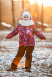 Six year old girl in warm clothes for a walk in the park, rays of the setting sun Stock Photography