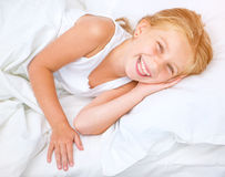 Six year old girl in a white bed Stock Image