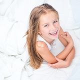 Six year old girl in a white bed Royalty Free Stock Images