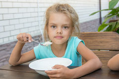 Six year old girl at a wooden table in yard eating porridge Stock Photo