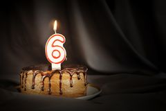 Six years anniversary. Birthday chocolate cake with white burning candle in the form of number Six. Dark background with black cloth royalty free stock images