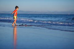 Six years old boy with surf board on exotic beach Royalty Free Stock Photography