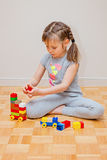 Six years old little girl playing with building blocks toys. Construction activity Royalty Free Stock Photo