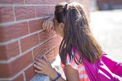 Six years old school girl cry beside brick wall. A six years old school girl cry beside brick wall stock photo
