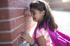 Six years old school girl cry beside brick wall. A six years old school girl cry beside brick wall royalty free stock photos